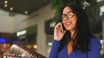 attractive brunette with beautiful face and big lips is sitting in shopping center. Talking by phone and smiling. Wearing blue dress , glasses and beautiful ring on her hand. Girl is very happy.