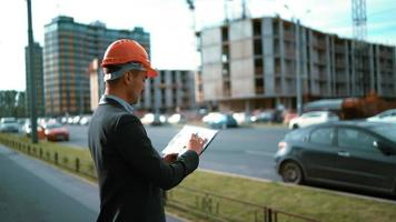 Obrero. arquitecto mira el plan de papel del edificio