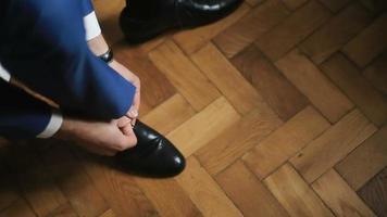 El novio lleva zapatos en el interior sobre el fondo de madera blanca