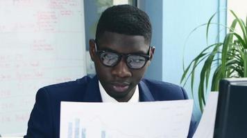 afroamericano en la oficina elegante traje lee una documentación importante video