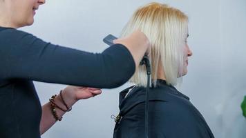 planchando el cabello de una mujer hermosa