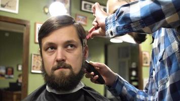 barbeiro fazendo corte de cabelo de atraente homem barbudo na barbearia