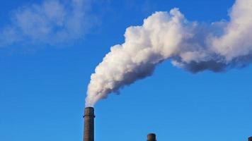 Pilha de fumaça de fábrica sobre fundo de céu azul video