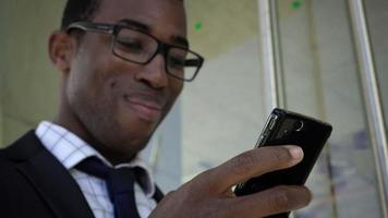 jovem empresário afro-americano usando telefone celular