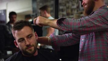 barbiere maschio che dà taglio di capelli del cliente in negozio