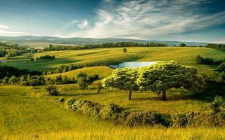 Beautiful hilly landscape with lake and blue cloudy sky photo
