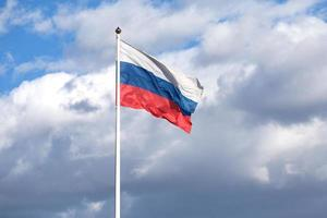 Russian flag on the flagpole waving on cloudy sky photo