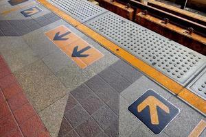 Arrow sign on floor at the sky train station