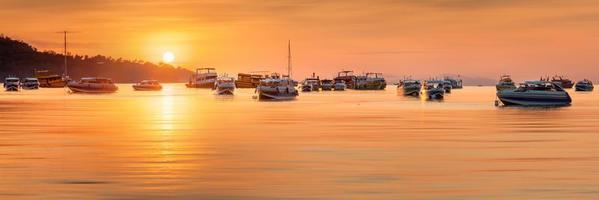 sunset with colorful sky and boat on the beach photo