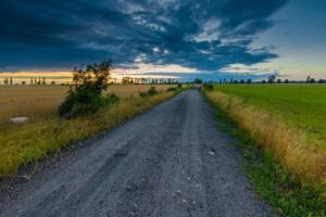 Landscape with dark stormy sky over fields at twilight photo