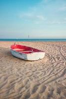 small fishing boat on the beach and blue sky