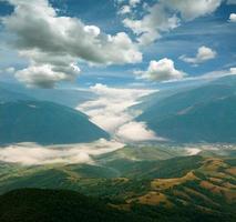 paisaje de colinas de montaña en la niebla bajo el cielo azul