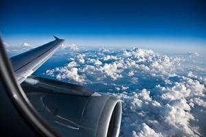 Window view of a planes wing above a billowy clouded sky