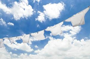 White clothes on a clothesline against a cloudy sky photo