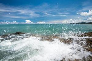 Olas del mar, línea de latigazo, roca de impacto en la playa foto