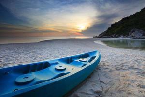 sea canoe kayak on sand beach with sun set sky