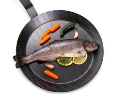 Marinated Rainbow trout with lemon on frying pan