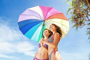 Sisters with rainbow umbrella on the beach
