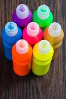 Colorful paint - bottles with colorful pigments on wooden background