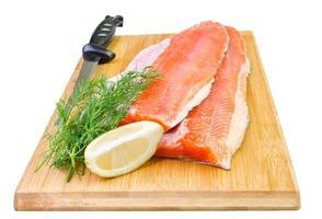 Filete de pescado de trucha arco iris con cuchillo sobre una placa de cocina