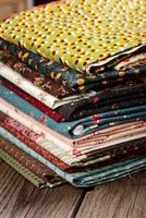 heap of cloth fabrics on wooden table photo