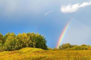 arco iris brillante sobre colinas brilladas con el sol.