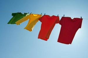 Colorful clothes hanging to dry in the blue sky photo