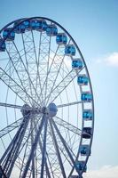 Ferris wheel above blue sky background