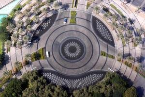 Symettrical roundabout surrounded by palm trees viewed from above photo