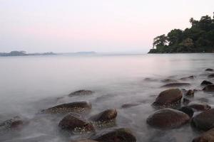 Hermosa playa de la provincia de Goa en la puesta de sol con piedras en foto