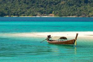 longtail boat in crystal clear turquoise water and tropical beach