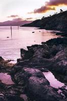 idílica vista de la playa rocosa al atardecer con cielo rosa foto