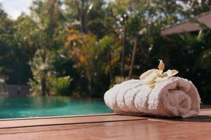 White towel near the pool with palm trees