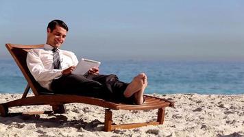 uomo d'affari sdraiato sulla spiaggia