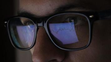Closeup of businessman in glasses analyzing market data information at night
