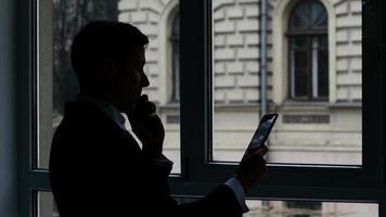 hombre de negocios de pie en la ventana, hablando por teléfono, ver información en la tableta. silueta video