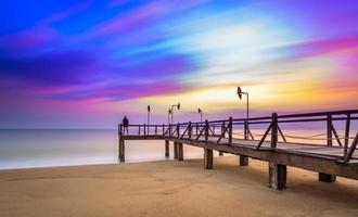 larga exposición de colorido amanecer y muelle de madera foto