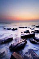 mar de roca costera y puesta de sol foto