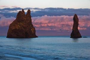 Rock formations and dramatic clouds on black beach at sunset