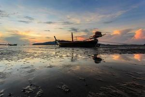 Silhouettes of longtail boat and sunrise in Phuket, Thailand