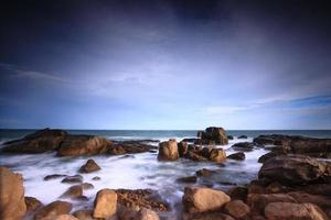 Waves crashing on rocky shore in the sunset photo