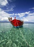 Fishing boat on crystal clear waters in Greece photo