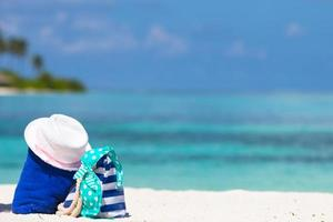 borsa blu, cappello di paglia, infradito sulla spiaggia bianca