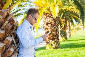 Young tourist under palm tree with mobile tablet pc. Positive.