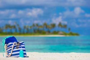 borsa blu, cappello di paglia, occhiali da sole e bottiglia di crema solare sulla spiaggia