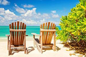Two beach chairs on tropical shore, horizontal composition photo