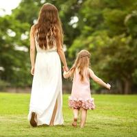 mother and daughter walking in the park, happy at sunset photo
