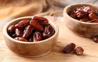 Fruits dates in wooden bowl  on  table photo