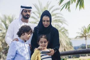 Middle Eastern Family Using Smart Phone Outdoors