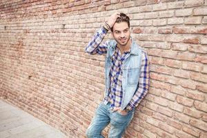 man leaning on a brick wall while fixing his hair